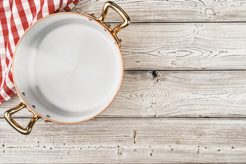Flatlay of copper cooking pot on wooden background