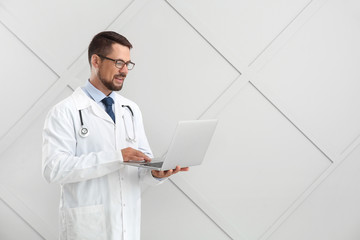Male doctor with laptop on light background