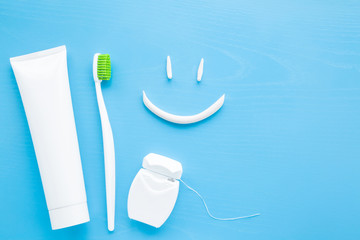 Toothbrush with green bristles, white tube of toothpaste, dental floss on pastel blue background. Smiley face created from paste. Happy for healthy teeth concept.