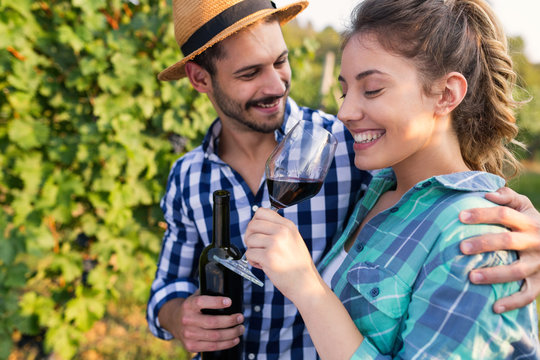 Woman and man in vineyard drinking wine
