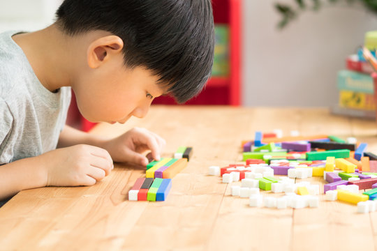 A little asian boy learning about numeracy, adding - subtracting and counting through colorful cuisenaire rods. Early math, Cognitive skills, Learning tools, Child development, Educational concept.