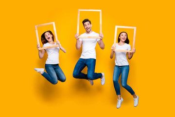 Full length body size view portrait of three nice attractive lovely cheerful cheery carefree person holding in hands frames having fun isolated over bright vivid shine yellow background