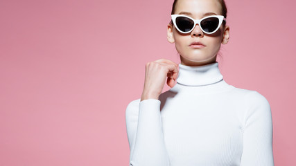 Fashion studio image of gorgeous elegant woman in white knitted golf and sunglasses posing over pink wall.