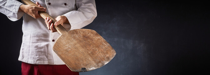 Chef holding an empty wooden pizza paddle