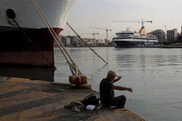 A man fishes as passenger ferries are moored during a 24-hour strike of Greece's seamen's federation PNO against austerity policies affecting their sector, at the port of Piraeus