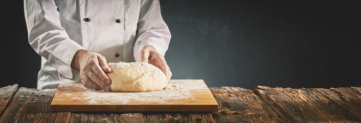 Chef or baker preparing a mound of raw dough