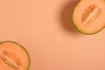Melon half on orange background. Creative layout made of fresh melon. Flat lay, top view, copy space