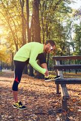Preparing for jogging in autumn colored park.