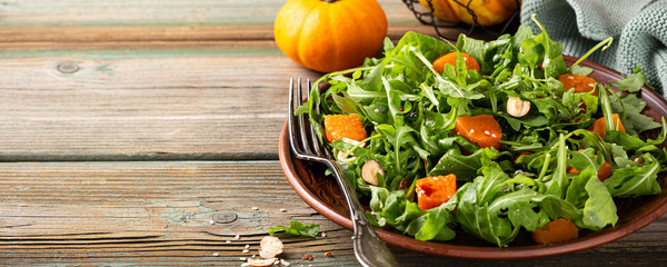 Paleo diet salad with arugula, baked pumpkin, hazelnut and sesame seeds on brown plate. Healthy food concept with copy space. Banner.
