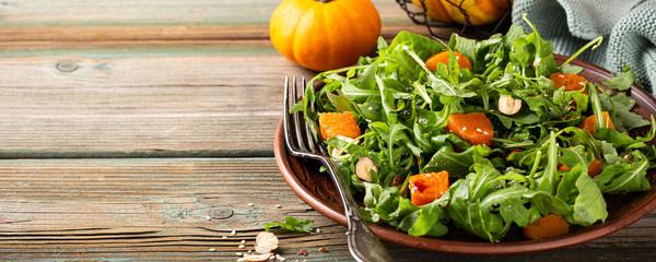 Salad diet paleo dengan arugula, labu panggang, kemiri dan biji wijen di atas piring cokelat.  Konsep makanan sehat dengan ruang fotokopi.  Spanduk.