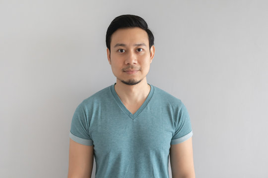 Normal straight face portrait of man in blue t-shirt on grey background.