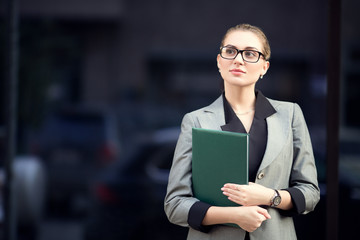 business woman in glasses and a suit holds a folder in her hands. Woman on the street waiting for a meeting