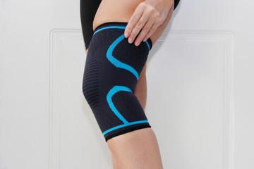 Closeup of a leg with one grip of a knee brace. Orthopedic knee pad. A woman wears a knee brace. Knee joint problem.