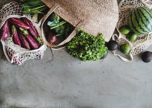 Eco-friendly lifestyle. Flat-lay of of grocery jute and net bags with fresh organic vegetables, greens, fruit from local farmers market, copy space. Zero waste, healthy, vegan and clean eating concept