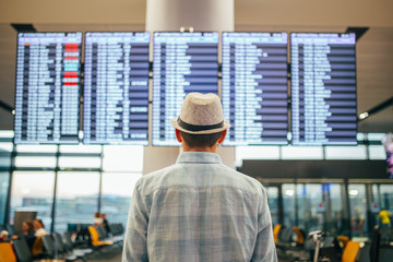Solo traveler - man standing inside airport terminal looking at a schedule.  Travel and transportation themed image.