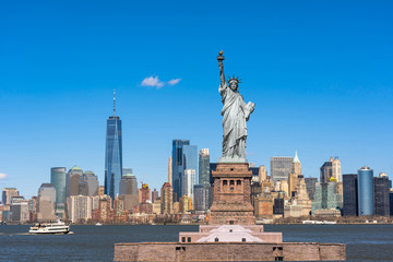 Fotomurales - The Statue of Liberty over the New York cityscape river side which location is lower manhattan, United state of America, USA, Architecture and building with tourist concept