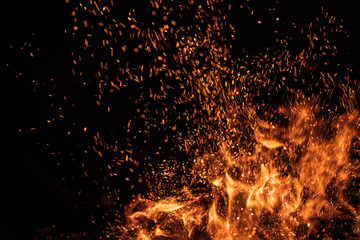 Burning sparks flying. Beautiful flames. Fiery orange glowing flying away particles on black...