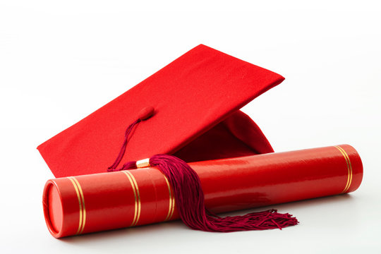 Academic accomplishment, completion certificate of higher education and associates degree conceptual idea with red tube holding a diploma and graduation cap or mortarboard isolated on white background