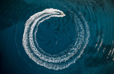 Speed boat in mediterranean sea making a cyrcle from bubbles, aerial view Fotomurales