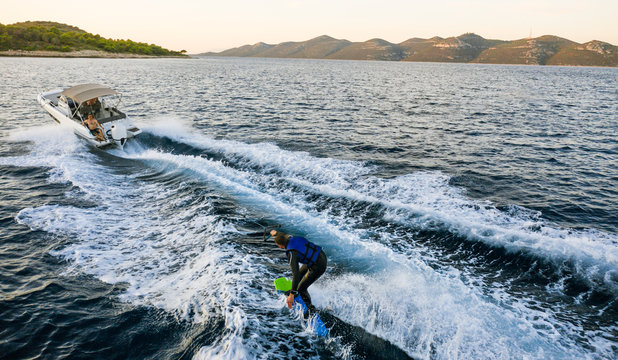Aerial photo of man practicing wakeboarding towed by speed boat in deep blue sea