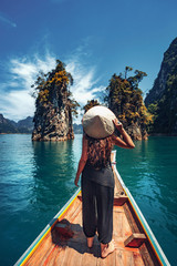 young woman tourist in asian hat on the boat at lake