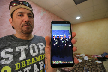 Hani al-Bazoni, who was deported from the United States to Iraq under U.S. President Donald Trump's strengthened immigration enforcement, shows the picture of his son, a U.S. sailor during an interview with Reuters at his home in Basra