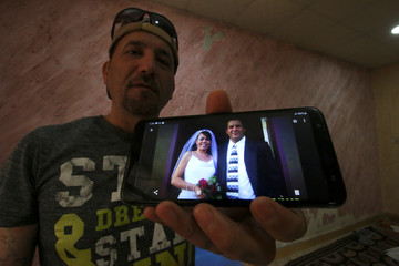 Hani al-Bazoni, who was deported from the United States to Iraq under U.S. President Donald Trump's strengthened immigration enforcement, shows a picture of his wedding with his mobile during an interview with Reuters at his home in Basra