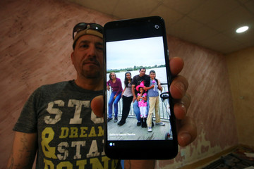 Hani al-Bazoni, who was deported from the United States to Iraq under U.S. President Donald Trump's strengthened immigration enforcement, shows a picture of his family with his mobile during an interview with Reuters at his home in Basra