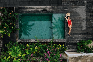 Aerial drone photo of happy Woman in red swimsuit relaxing near private pool with flowers and greenery around, Bali. Tropical background and travel concept.