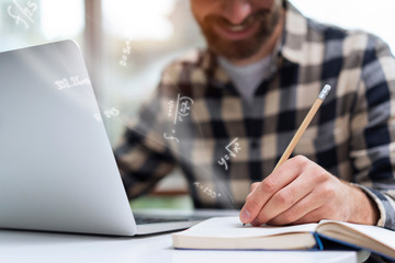 Close-up on a young man's hand while he is keeping mathematical notes in his notebook holding a pencil. Communicate about education, college, using pencil to write while working along with a laptop