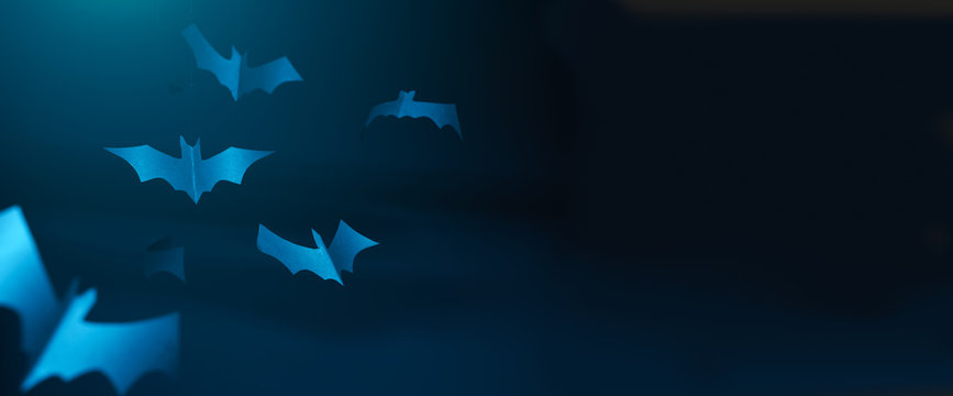 Halloween photo of blue paper bats on blank dark blue background.