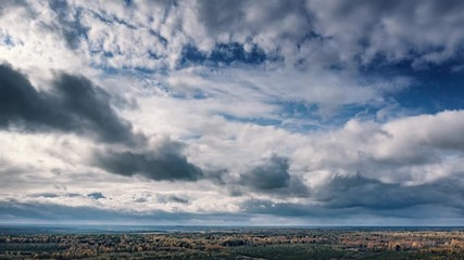 Fotobehang - Beautiful clouds moving in blue sky over forest landscape. Aerial timelapse, 4K UHD.