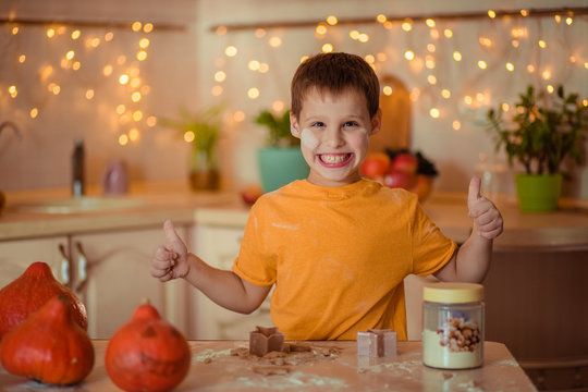 happy seven year old happy boy in the kitchen preparing gingerbread cookie and showing class. Waiting for Halloween