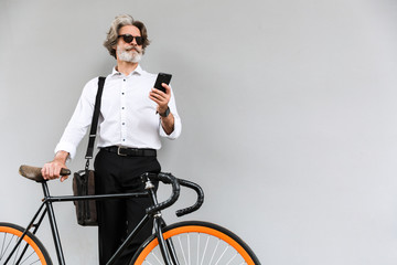 Photo of caucasian old businessman using cellphone while standing