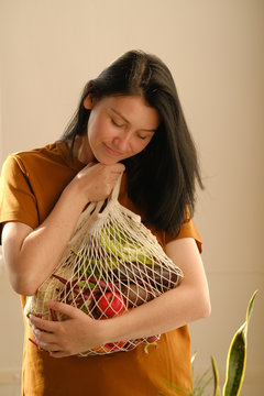 Young woman holds string bag mesh with vegetables and fruits. Plastic free concept