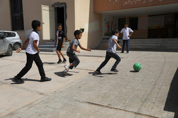 Libyan students play football during the summer school programme at a local school in Tripoli