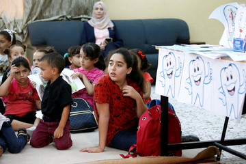 Libyan students attend a class for dental health, during the summer school programme at a local school in Tripoli