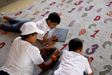 Libyan students practice drawing and calligraphy skills during the summer school programme at Ben Ashour school in Tripoli