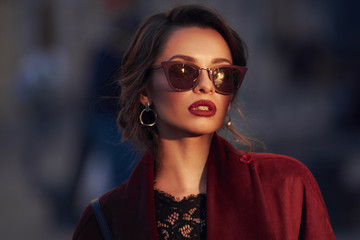 Closeup portrait of young elegant woman wearing sunglasses. Pretty girl with hairstyle and makeup. Outdoor portrait. Sunset light. Wall mural