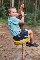 Happy boy riding on the zip line in rope park in forest while spending summer vacation. Real people, authentic situations