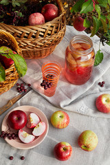 Fresh organic red apple in the basket, cutted slices on the plate apple juice in the glass