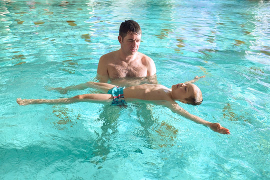 Happy father and son swimming lesson in the pool. Child learning