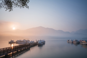 Beautiful tranquil landscape at Sun Moon lake in Nantao, Taiwan. Pier with boats and background of foggy mountains. Concept of peaceful, traanquility of nature. Wall mural