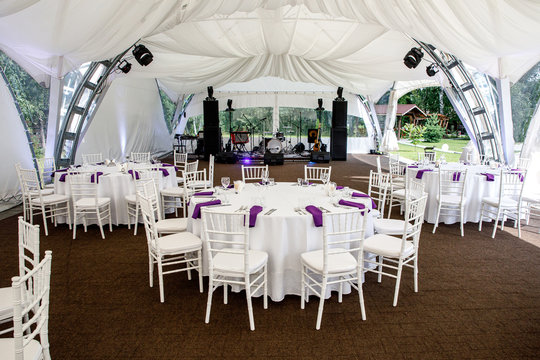 Interior of a event tent decoration ready for guests. Served round banquet table outdoor in marquee