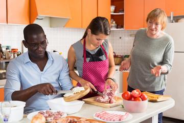 Upset couple preparing dinner with elderly woman reprimanding them