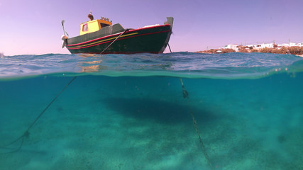 Above and below underwater photo of colourful fishing boat in turquoise clear Greek island sea