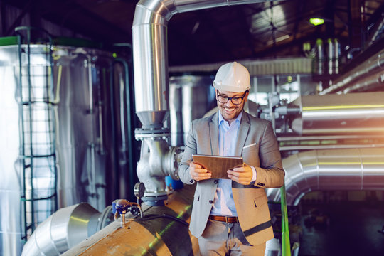 Handsome smiling caucasian supervisor in suit and with helmet on head using tablet while standing in power plant.