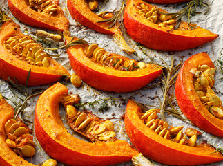 Baked Pumpkin slices with the addition of olive oil, spices and herbs on baking paper, close-up,...