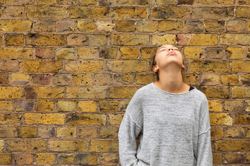 Depressed girl stand in front of a brick wall looking up