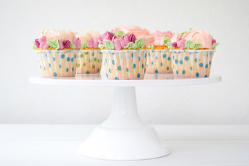 Cupcakes with colorful cream flowers on white background. Picture for a menu or a confectionery catalog.